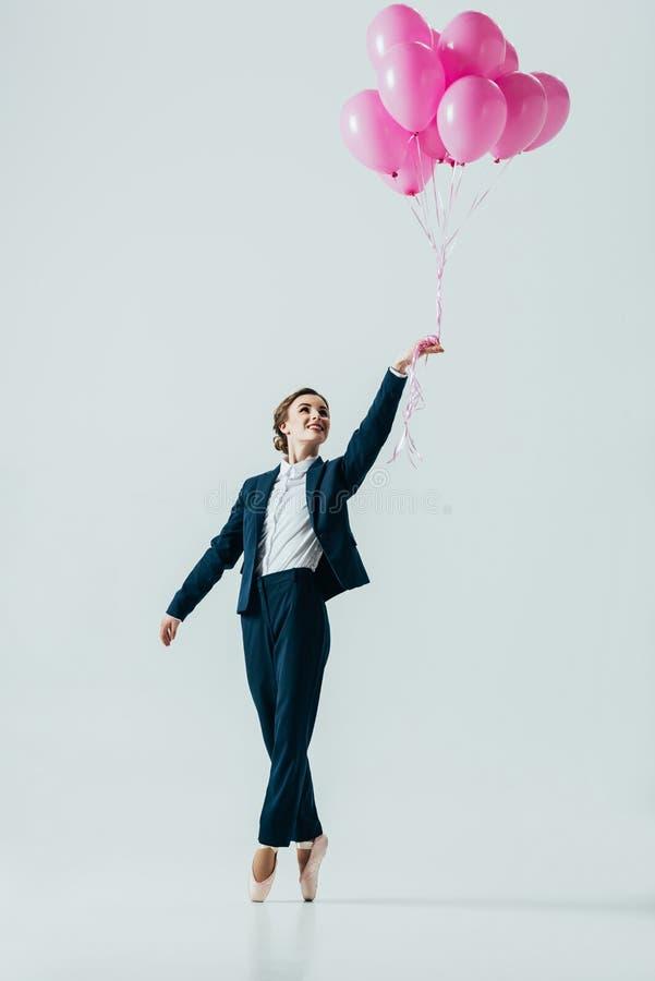 onderneemster die in kostuum en balletschoenen roze ballons houden stock afbeelding