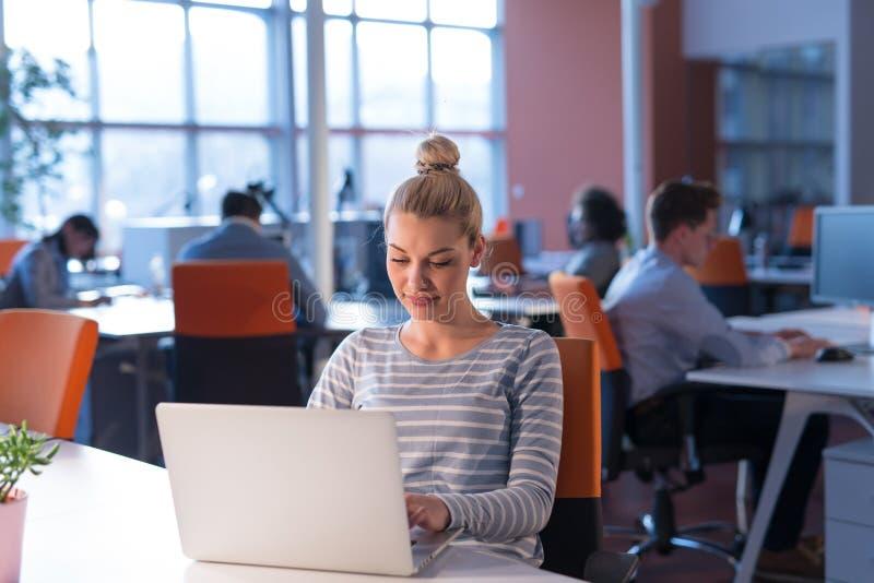 Onderneemster die laptop in startbureau met behulp van royalty-vrije stock fotografie