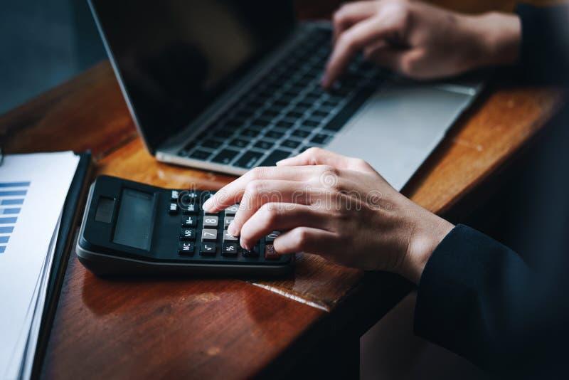 Onderneemster die met calculator en laptop computer werken om financieel gegevensrapport te berekenen Financiële zaken en boekhou royalty-vrije stock foto