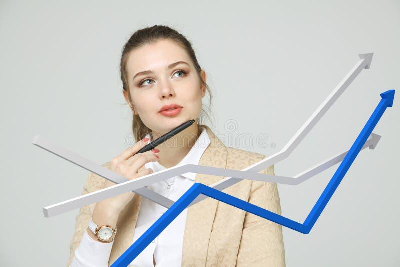 Onderneemster die met de groeigrafiek aan grijze achtergrond werken royalty-vrije stock afbeelding