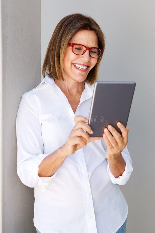 Onderneemster die met digitale tablet glimlachen stock foto's