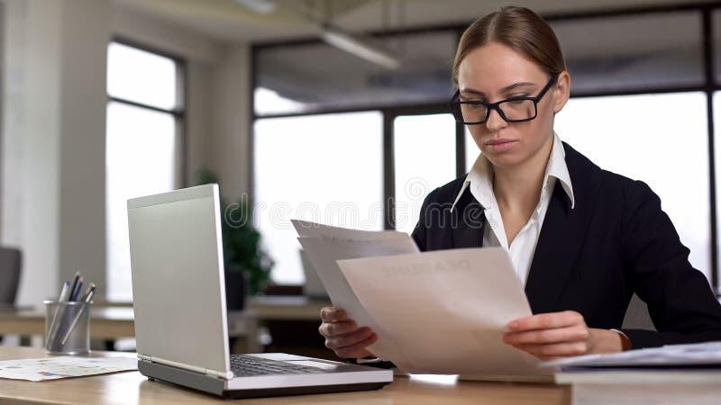 Onderneemster die met documenten werken, die jaarlijks financieel verslag in bureau controleren stock foto's