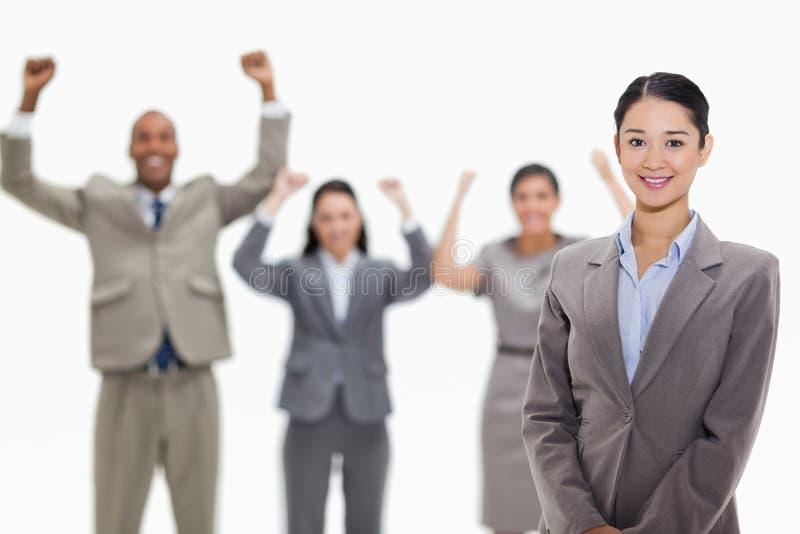 Onderneemster die met enthousiaste medewerkers glimlachen royalty-vrije stock foto's