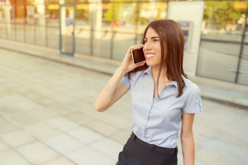 Onderneemster die mobiele telefoon met behulp van stock foto's