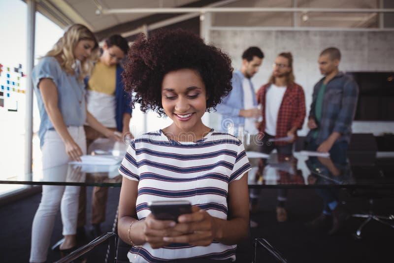 Onderneemster die mobiele telefoon met collega's op achtergrond met behulp van stock fotografie