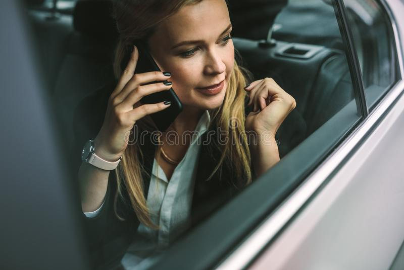 Onderneemster die op cellphone in auto spreken stock afbeelding