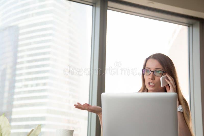 Onderneemster die op cellphone in bureau debatteren royalty-vrije stock foto