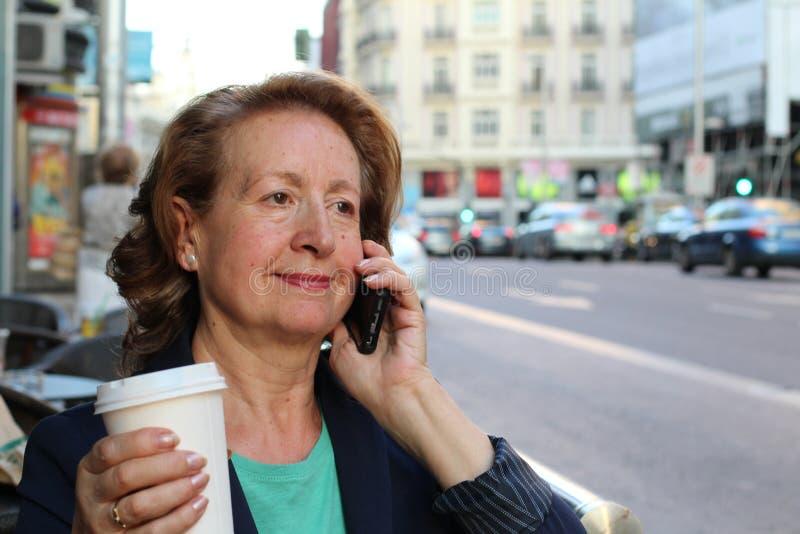 Onderneemster die op cellphone terwijl het spreken op slimme telefoon lopen Gelukkige glimlachende Kaukasische bedrijfs bezige vr stock foto