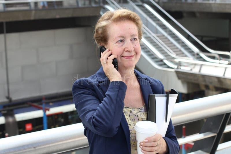 Onderneemster die op cellphone terwijl het spreken op slimme telefoon lopen Gelukkige glimlachende Kaukasische bedrijfs bezige vr royalty-vrije stock afbeeldingen