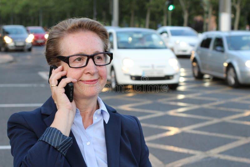 Onderneemster die op cellphone terwijl het spreken op slimme telefoon lopen Gelukkige glimlachende Kaukasische bedrijfs bezige vr stock afbeelding