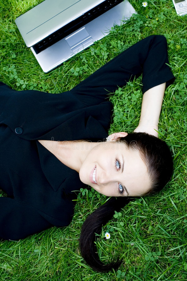 Onderneemster die op gras ligt stock fotografie