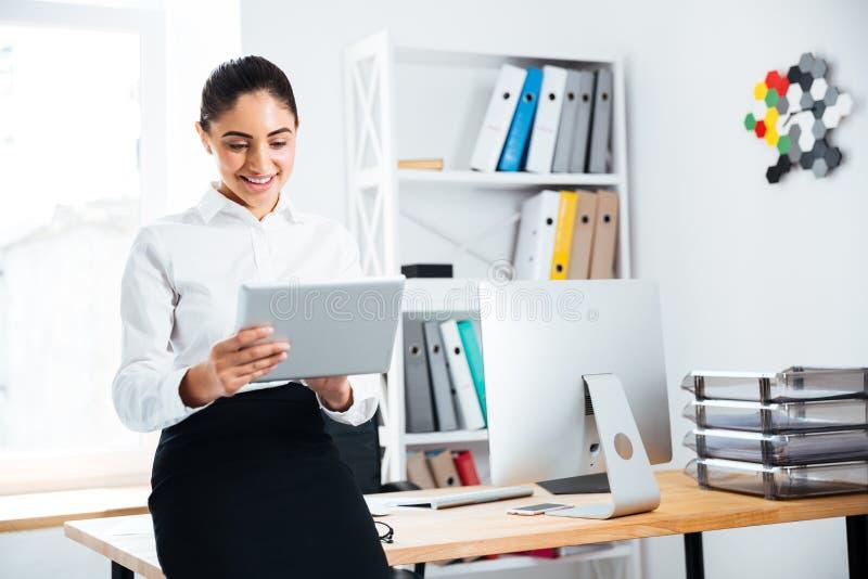 Onderneemster die op het bureau leunen en PC-tablet gebruiken stock fotografie