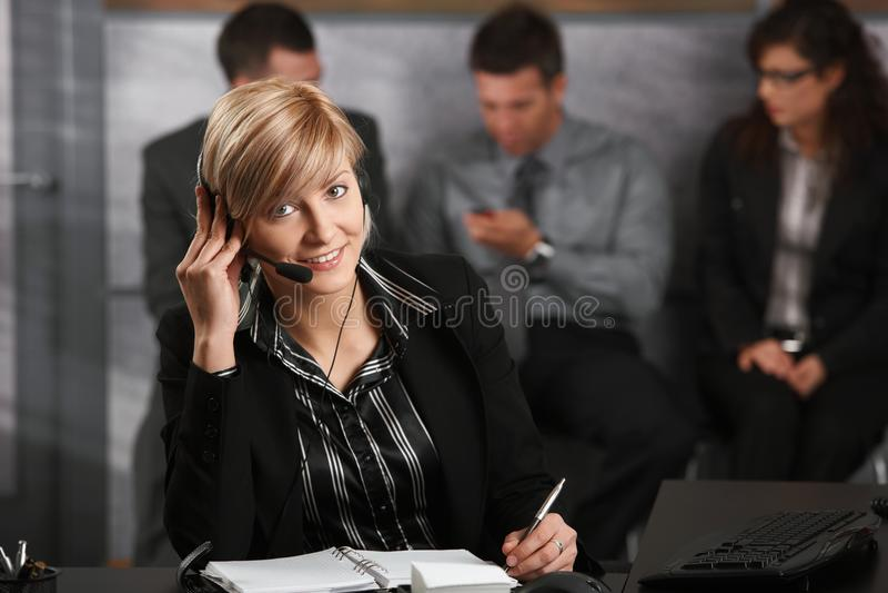 Onderneemster die op hoofdtelefoon spreekt stock afbeeldingen