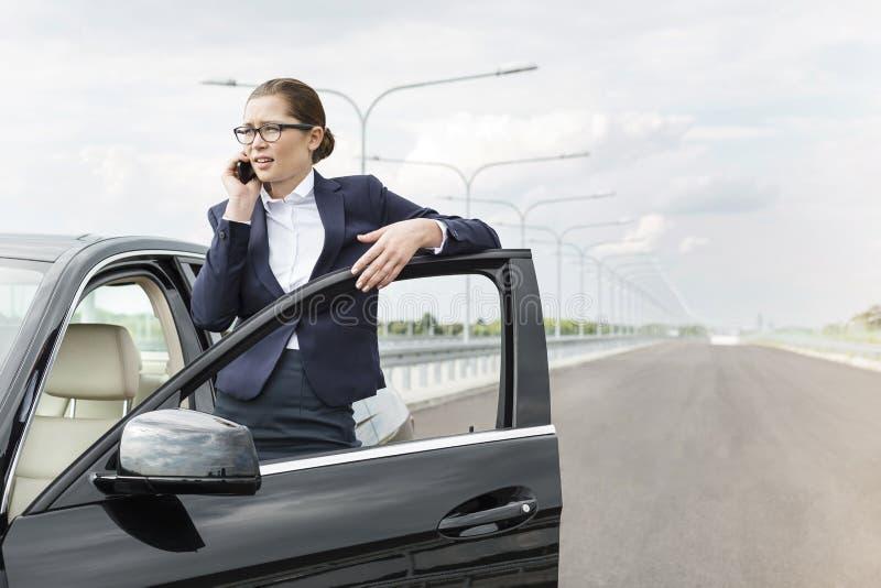 Onderneemster die op smartphone spreken terwijl status door auto op weg stock afbeeldingen