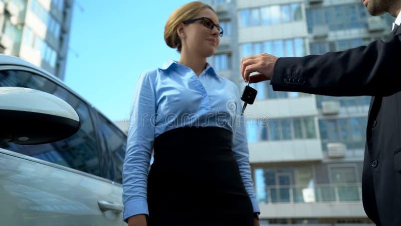 Onderneemster die sleutels ontvangen aan luxeauto van handelaar, autolening of aankoop royalty-vrije stock foto's