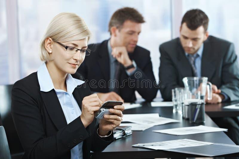 Onderneemster die smartphone in bureau gebruikt stock foto's