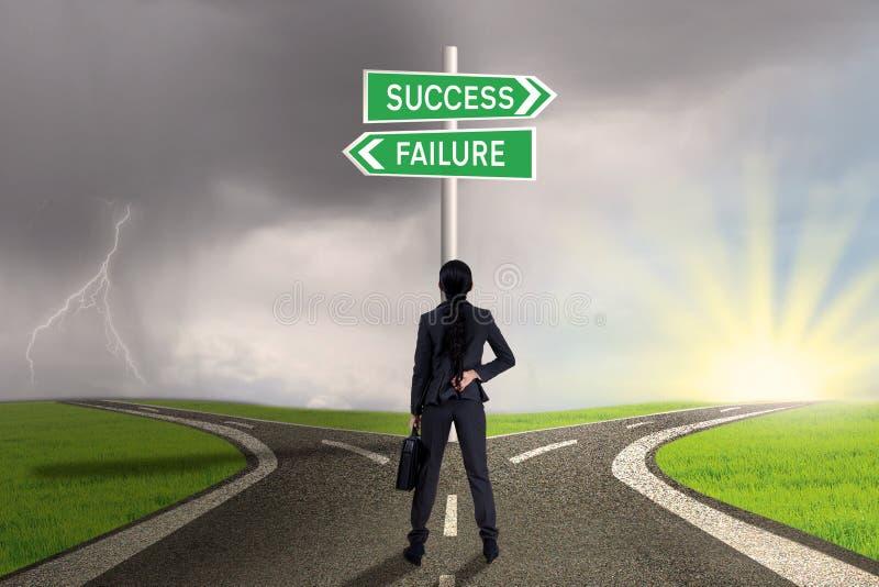 Onderneemster die teken van succes of mislukking bekijken stock afbeelding