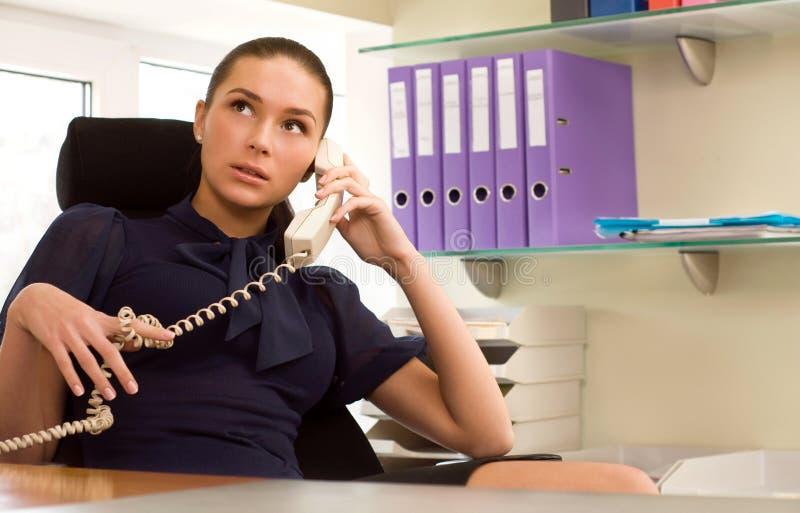 Onderneemster die telefonisch in bureau roept stock foto's