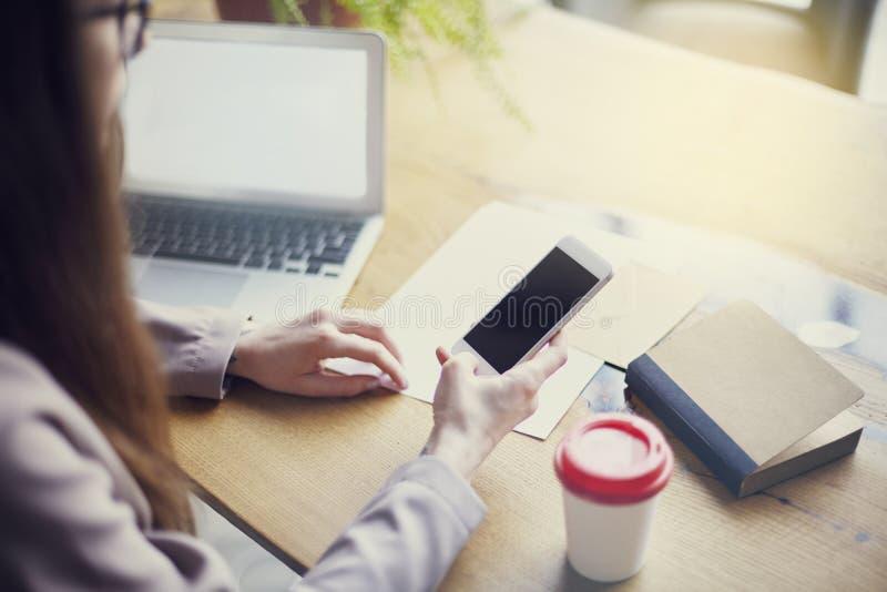 Onderneemster die telefoon met behulp van terwijl het zitten in zijn bureau met houten lijst Lege ruimte voor lay-out stock fotografie
