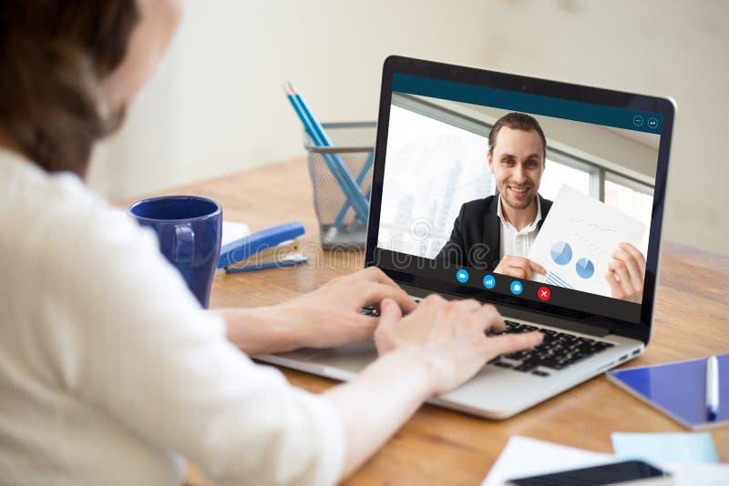 Onderneemster die tot videovraag maken aan zakenman die document tonen stock afbeelding