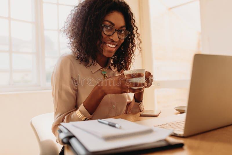 Onderneemster die van een kop van koffie genieten terwijl het werken aan laptop a stock foto's