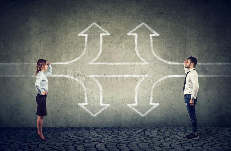 Onderneemster en de zakenman die de toekomst de onderzoeken als een kruispuntpijlen verdelen op drie verschillende manieren het v royalty-vrije stock afbeeldingen