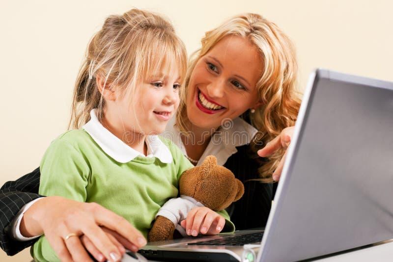 Onderneemster en moeder die jong geitje Internet tonen royalty-vrije stock afbeeldingen