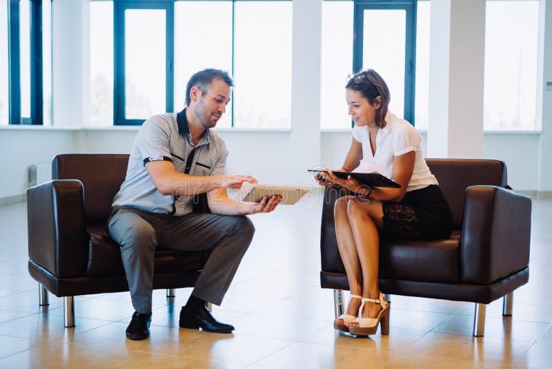Onderneemster en zakenman de zitting op stoelen bespreekt bedrijfsideeën royalty-vrije stock afbeelding