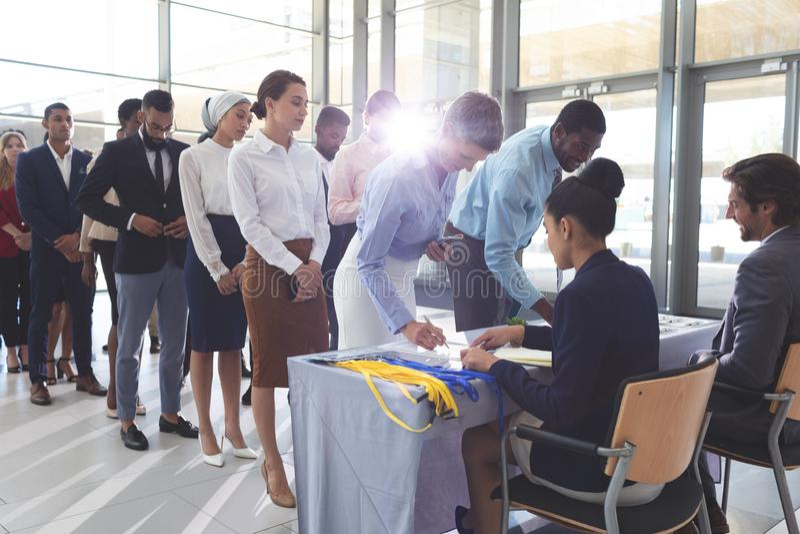 Onderneemster en zakenman die binnen bij de lijst van de conferentieregistratie ondertekenen stock foto
