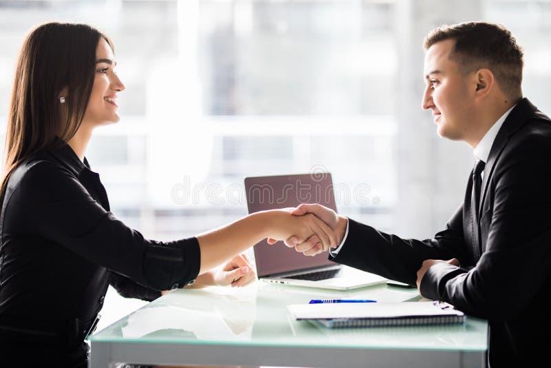 Onderneemster en zakenman het schudden overhandigt de lijst met laptop en documenten op het kantoor, prettige commerciële vergade stock afbeeldingen