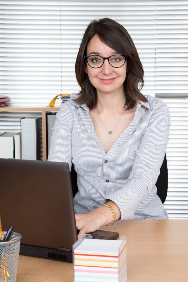 Onderneemster gebruikend laptop bij de vrouwenlevensstijl van de bureauwerkplaats en kijkend camera met glimlach royalty-vrije stock afbeeldingen
