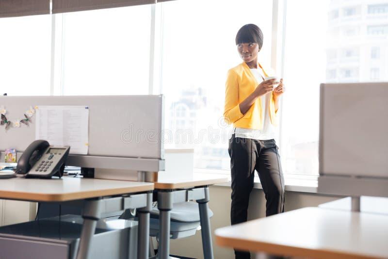 Onderneemster het drinken koffie in bureau stock foto