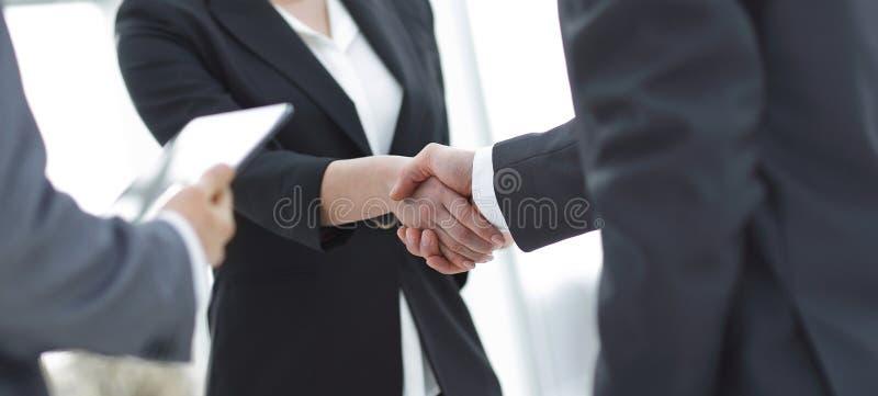 Onderneemster het schudden handen met businssman tijdens een vergadering royalty-vrije stock foto