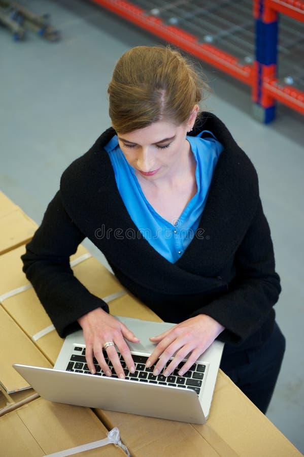 Onderneemster het typen op laptop computer in pakhuis stock fotografie