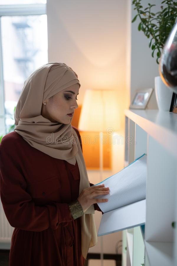 Onderneemster hijab en de modieuze documenten die van de blouselezing dragen stock foto's