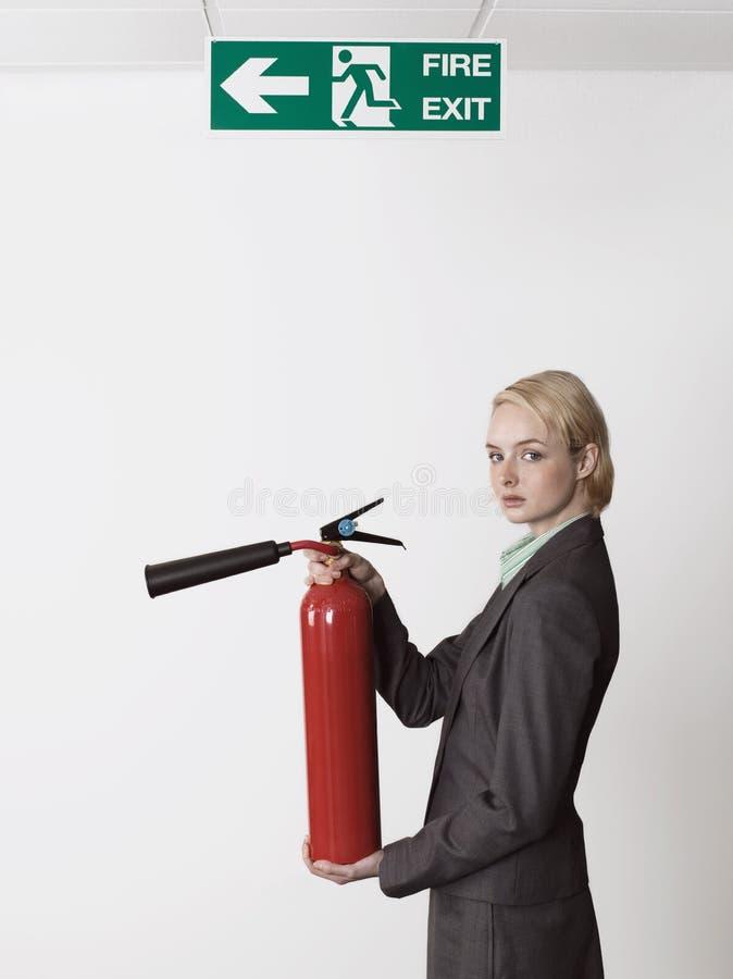 Onderneemster Holding Fire Extinguisher onder Uitgangsteken stock afbeeldingen