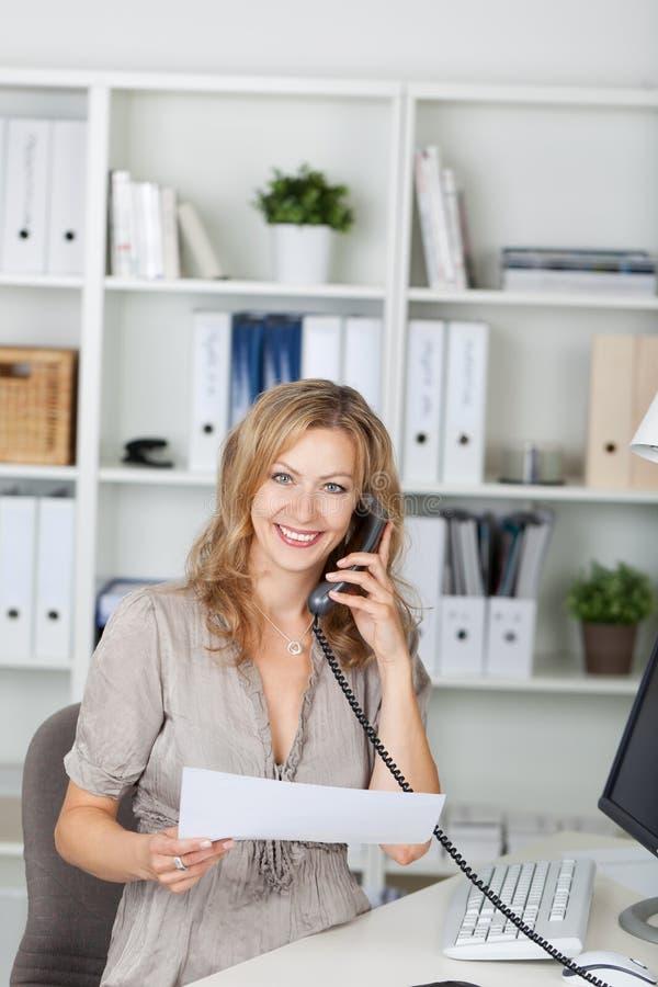 Onderneemster Holding Paper While die op Landline Phon communiceren stock afbeelding