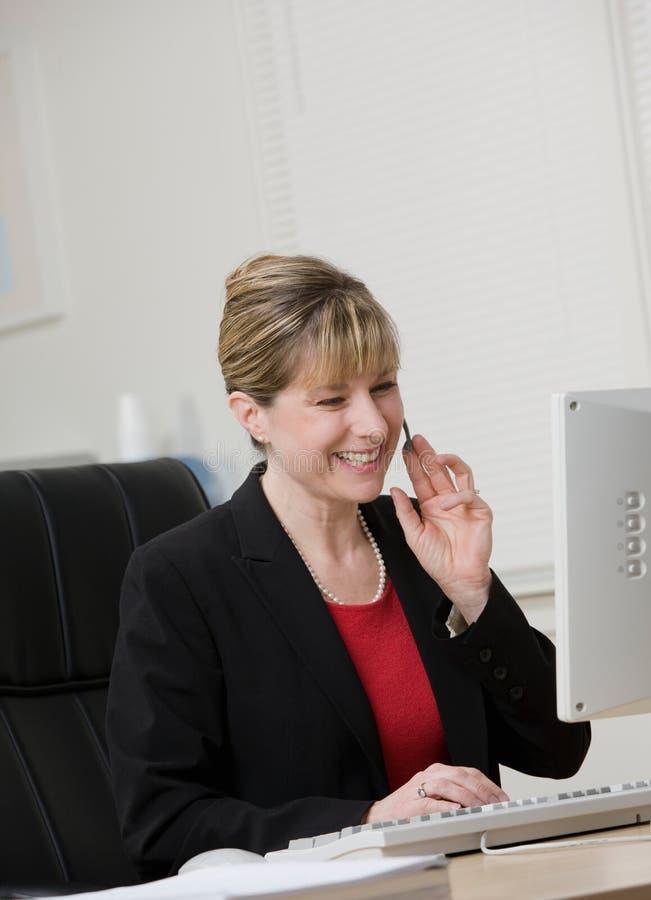 Onderneemster in hoofdtelefoon die bij computer werkt stock foto's
