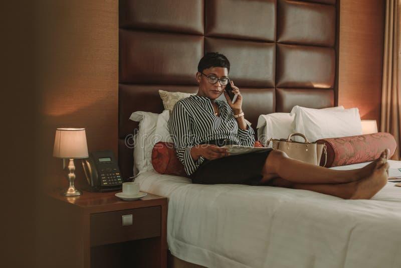 Onderneemster in hotelruimte met krant die over telefoon spreken stock foto