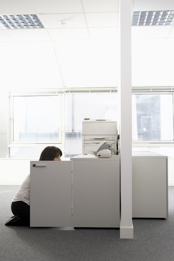 Onderneemster Kneeling In Front Of Open Cabinet stock fotografie