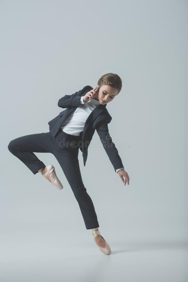 onderneemster in kostuum en balletschoenen die en op smartphone dansen spreken stock foto