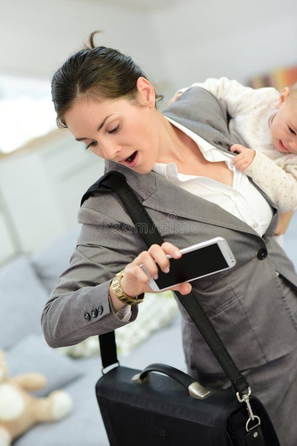 Onderneemster laat voor het werk die haar baby houden stock fotografie