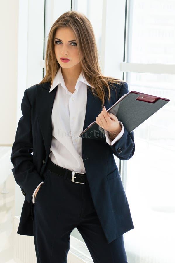 Onderneemster in man kostuum & overhemd die met pen bij haar gestileerde bureaumanier schrijven royalty-vrije stock afbeeldingen