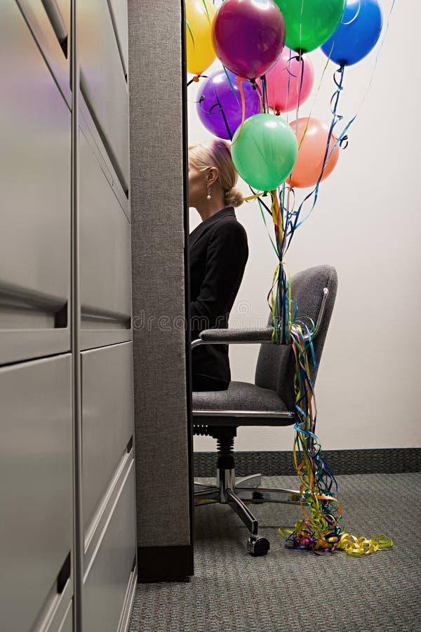 Onderneemster met bos van ballons wordt gezeten die stock afbeelding