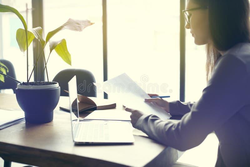Onderneemster met documentendocument blad in zolder modern bureau, die aan laptop computer werken Team die, bedrijfsmensen werken stock fotografie