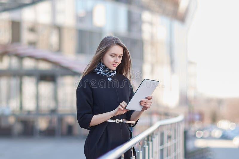 Onderneemster met een digitale tablet, die zich dichtbij het commerci?le centrum bevinden stock afbeelding