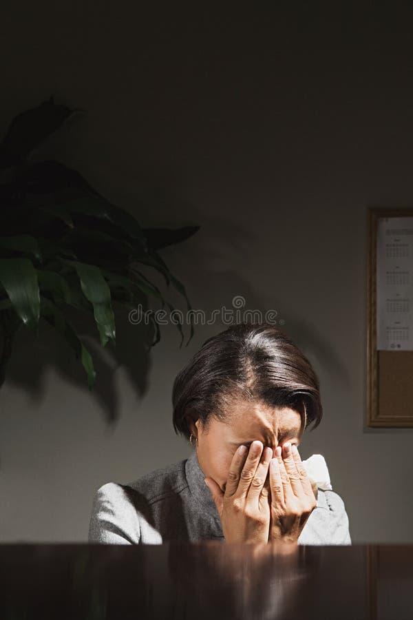 Onderneemster met haar hoofd in haar handen stock foto
