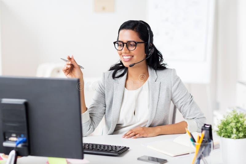 Onderneemster met hoofdtelefoon en computer op kantoor royalty-vrije stock afbeelding