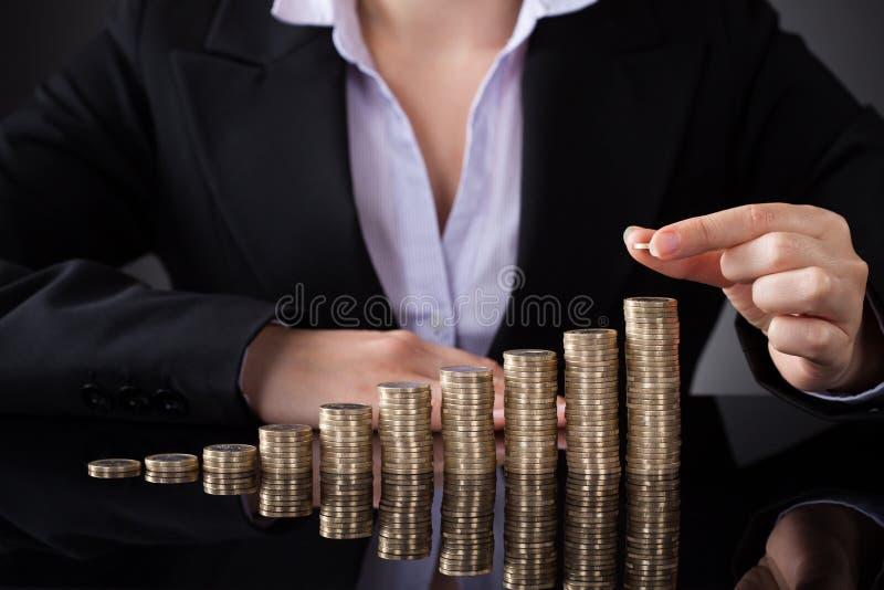 Onderneemster met rij van muntstukken stock foto's