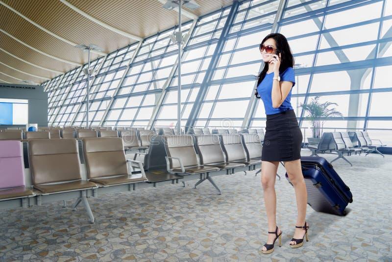 Onderneemster met smartphone in de luchthaven stock afbeeldingen